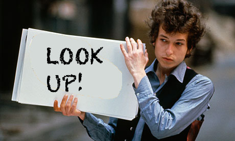 Bob Dylan holding sign saying Look up!
